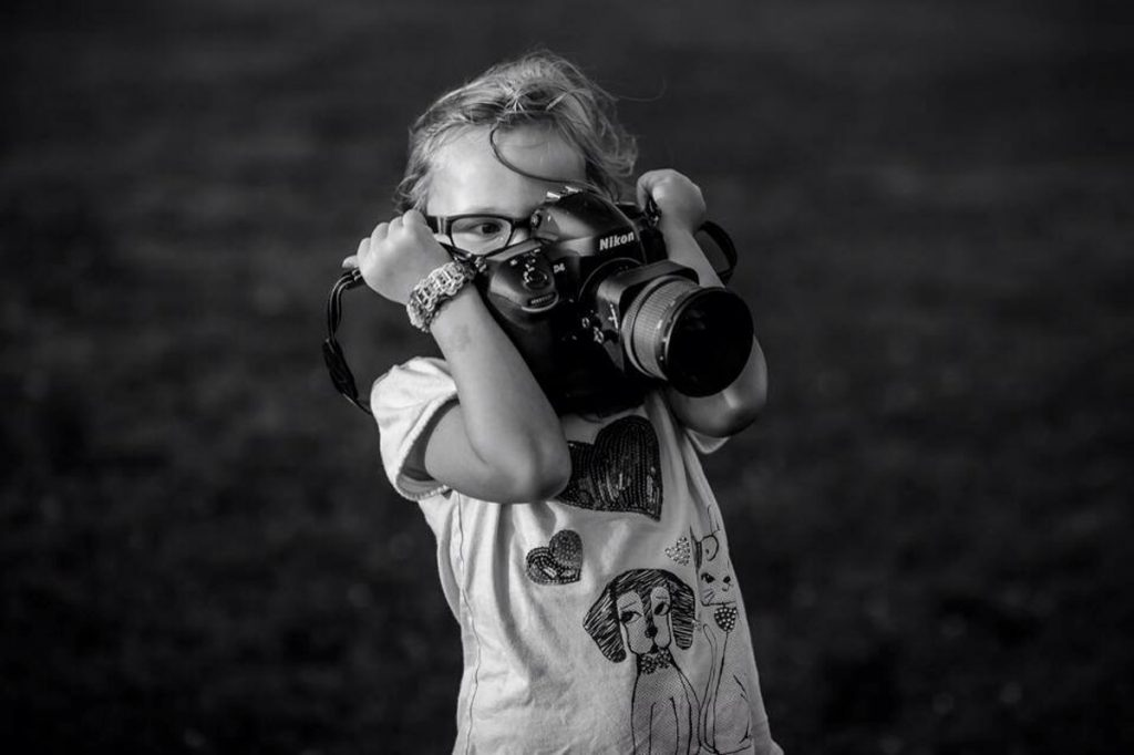 female child taking picture with camera