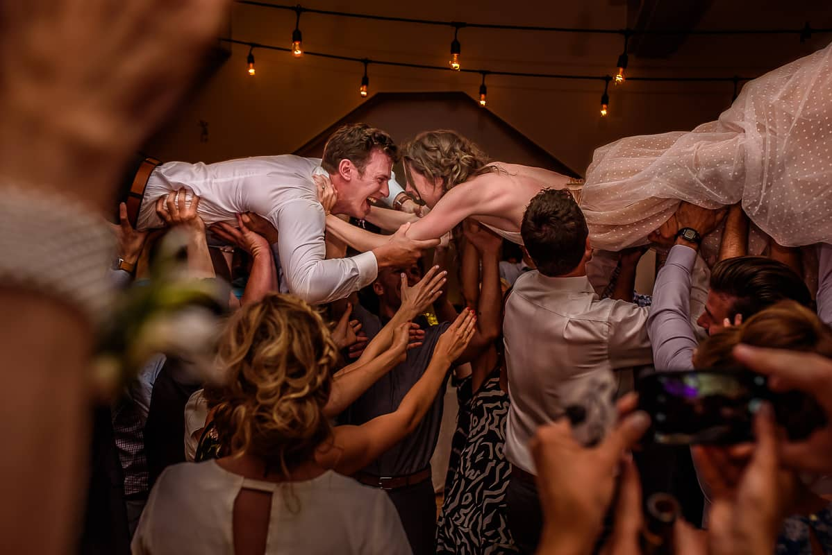 bride and groom being lifted up by people at a wedding