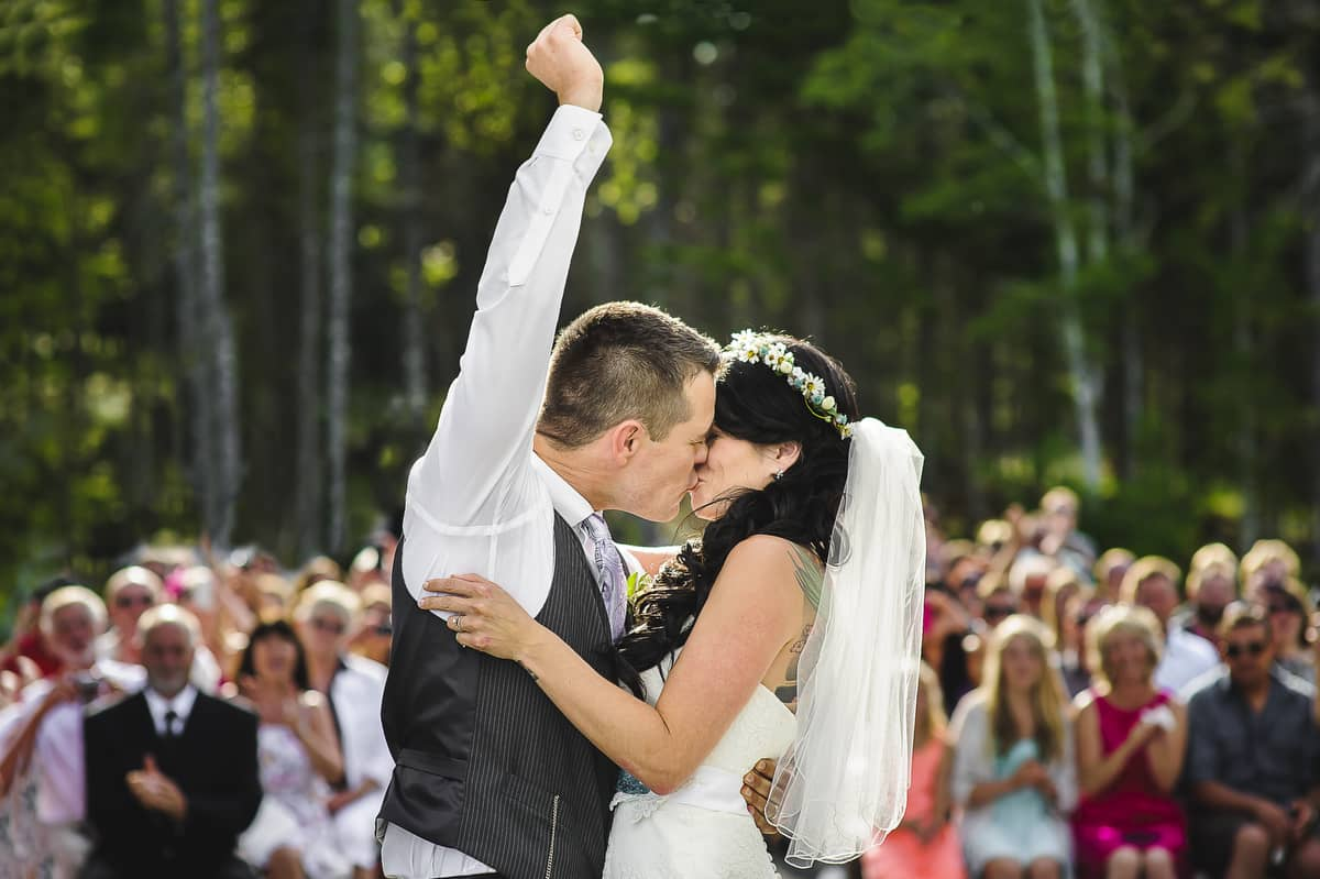 bride and groom kissing while groom fist pumps